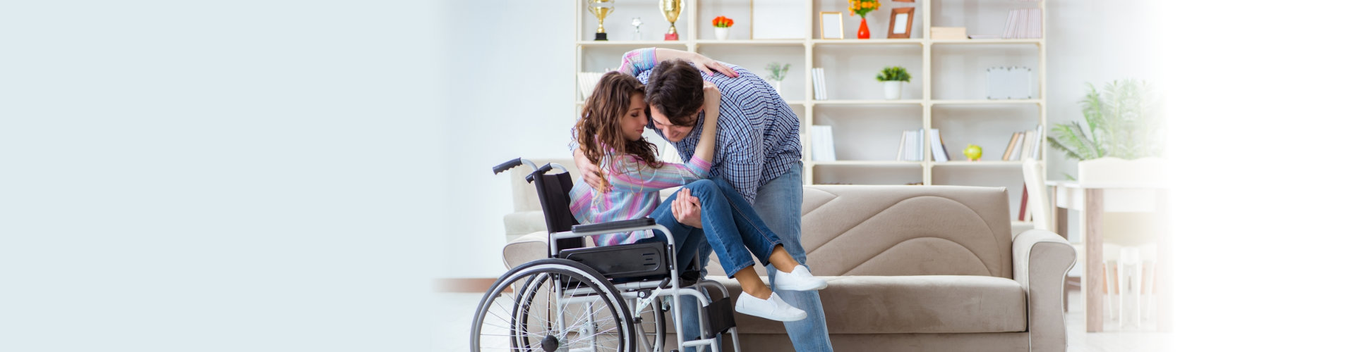 man carrying a woman from her wheelchair